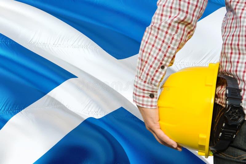 Szkocki inżynier trzyma żółtego zbawczego hełm z machać Szkocja chorągwianego tło Budowy i budynku poj?cie zdjęcia royalty free