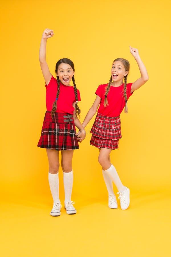 Szkocki styl Dzieciak dziewczyny odzieży w kratkę suknie ?wi?to narodowe Mundurek szkolny Rozochocony przyjaciel uczennic skakać obraz royalty free