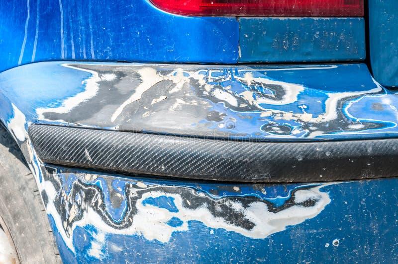 Szkoda na błękitnym porysowanym samochodowym zderzaku z uszkadzającą, strugającą farbą w i obraz royalty free