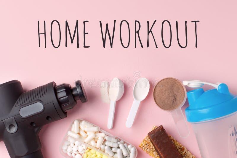 Szkolenie w domu, blokada Terapeutyczny perkusyjny pistolet masażowy, posiłek, pigułki, bar energii sportowej na różowym tle - ko zdjęcie stock