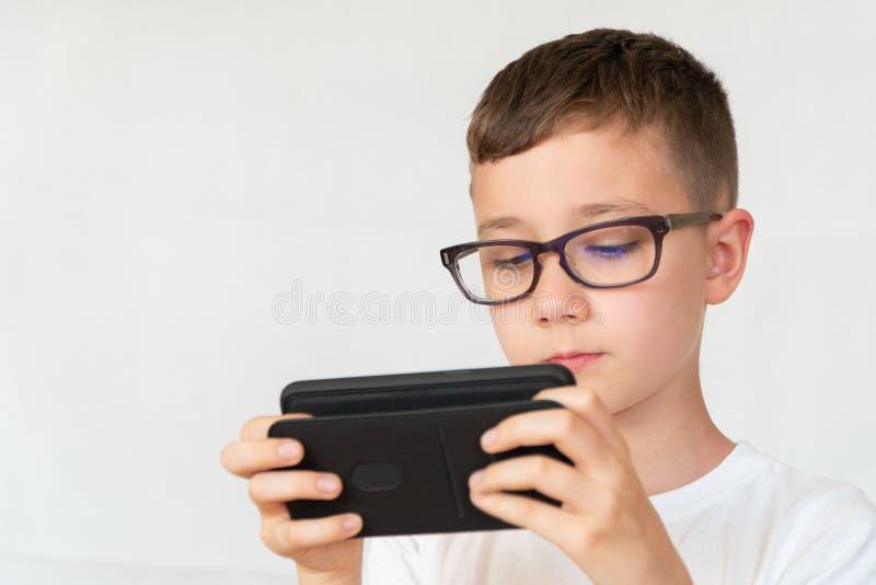 Szkolna chłopiec patrzeje przystojnego smartphone wideo w szkłach, obraz royalty free