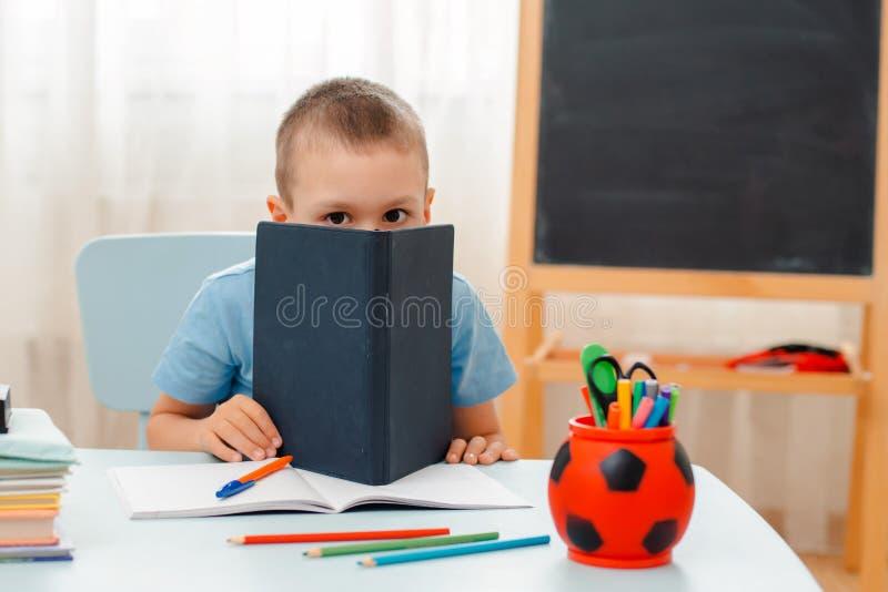 Szkolna chłopiec siedzi sali lekcyjnej łgarskiego biurko w domu wypełniał z książka stażowego materiału uczniem śpi gnuśnego zanu zdjęcia royalty free