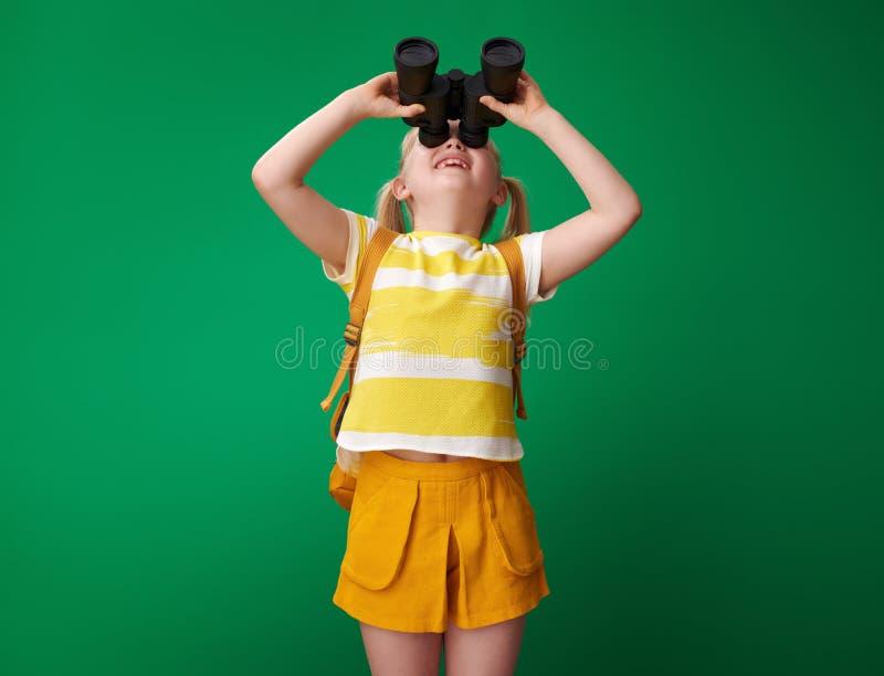 Szkolna dziewczyna przyglądająca przez lornetek odizolowywać na zieleni up zdjęcie royalty free