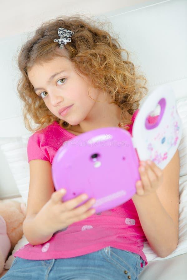 Szkolna dziewczyna trzyma elektroniczną książkę fotografia stock