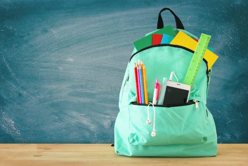 Szkolna torba z materiały i notatnikami przed blackboard tylna koncepcji do szkoły zdjęcie stock