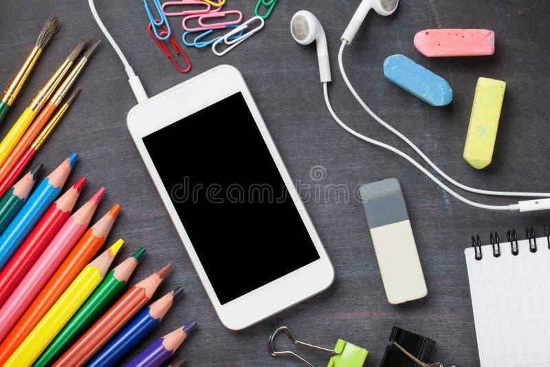 Szkolne dostawy i smartphone na blackboard tle zdjęcia royalty free