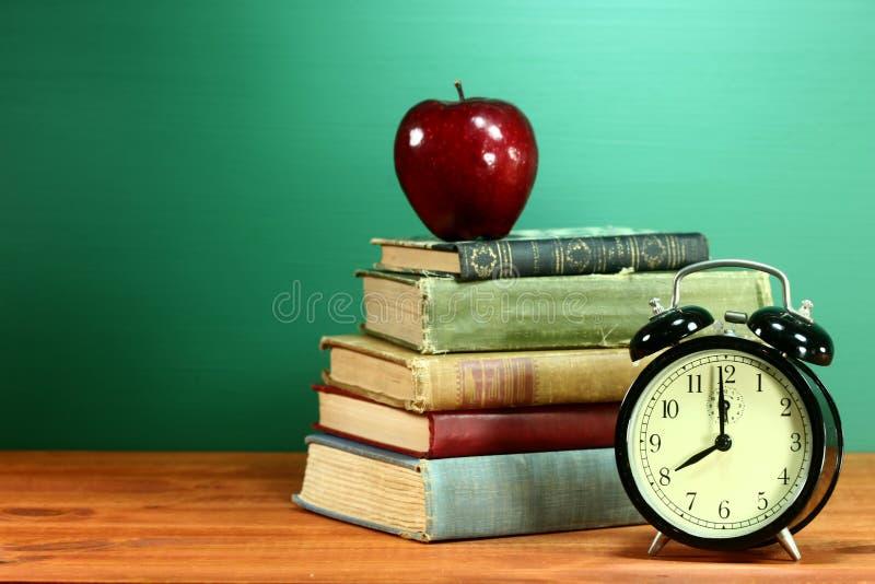 Szkolne książki, Apple i zegar na biurku przy szkołą, zdjęcie stock