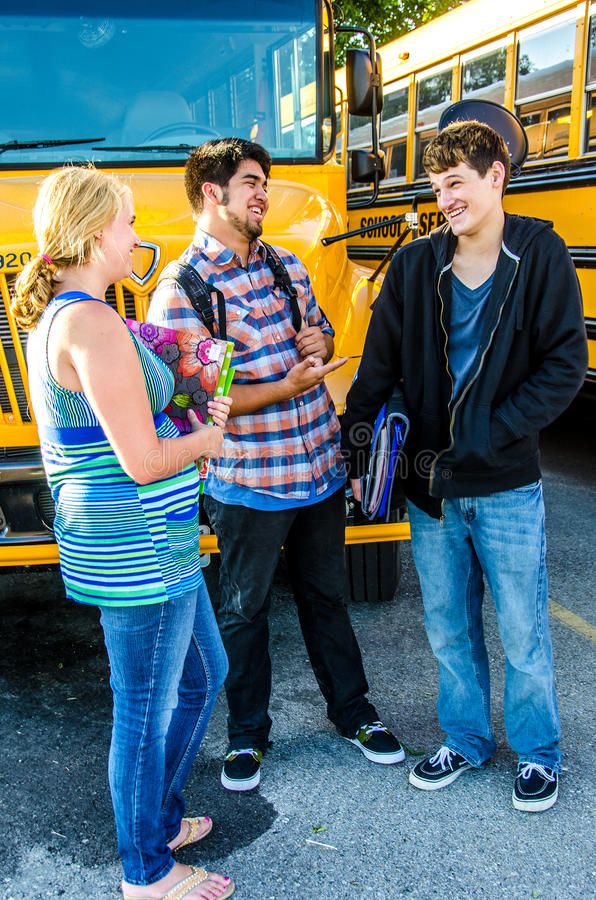 Szkolnego wieka nastolatkowie opowiada przed autobusem fotografia royalty free