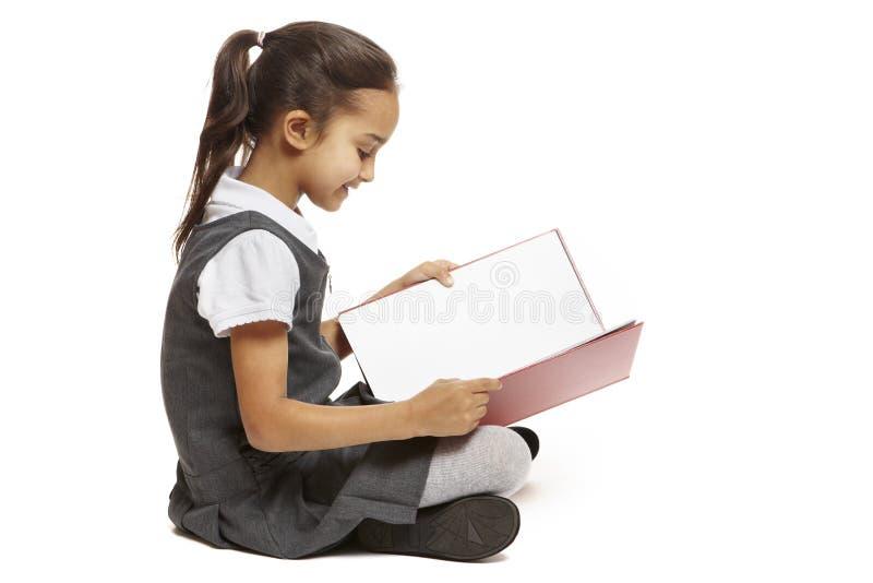 Szkolnej dziewczyny siedząca czytania książka zdjęcie royalty free