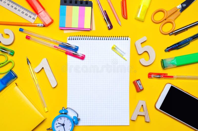 Szkolni akcesoria na biurku na żółtym tle jabłko rezerwuje pojęcia edukaci czerwień materiały zegarki, barwioni pióra, telefon, m fotografia stock