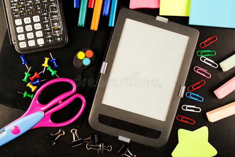 Szkolni akcesoria na czarnym drewnianym stole z elektroniczną książką fotografia stock