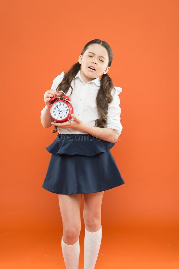 Szkolny alarm Szczęśliwy dziewczyna chwyta budzika liczenie dla lunchu czasu Szkolny czas Czas i?? szko?a Dziecko edukacja obrazy royalty free