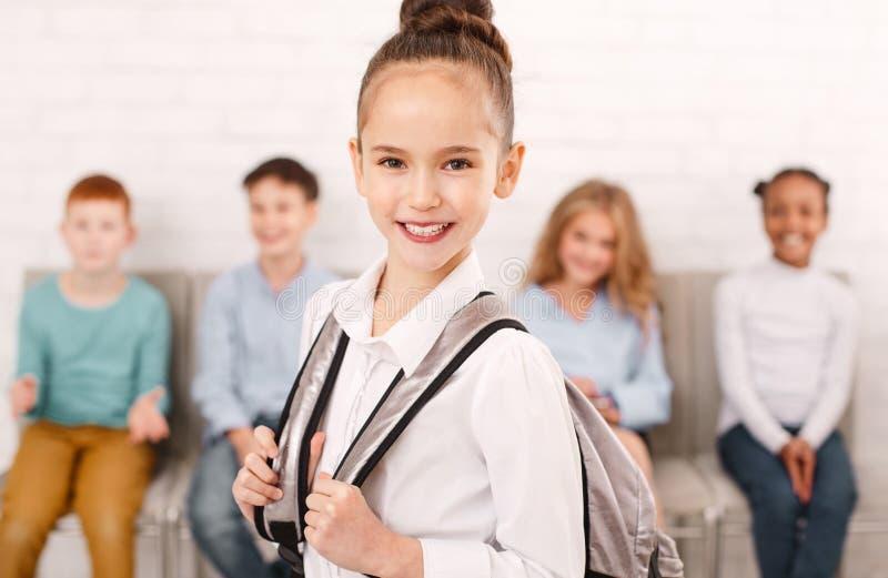 Szkolny dziewczyny przewożenia plecak z przyjaciółmi na tle obrazy royalty free