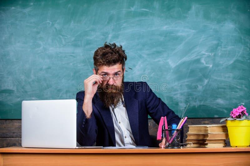 Szkolny egzaminu pojęcie Egzaminator wątpienia pełno siedzi przy stołowym chalkboard tłem Chytry examinator ono waha się o ocenie obrazy stock