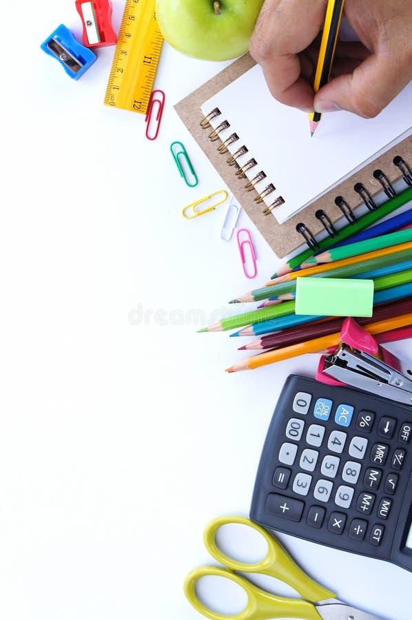 Szkolny materiały i ludzki ręki writing na małym notatniku na białym tle zdjęcia stock