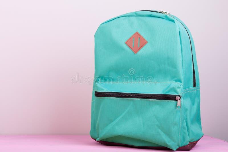 szkolny plecak jest na różowym drewnianym stole na różowym tle zdjęcia royalty free