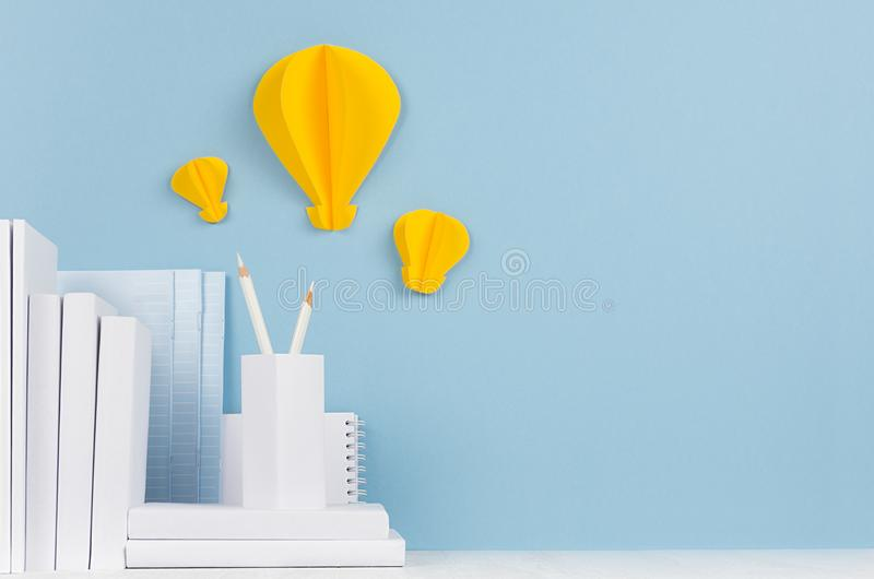 Szkolny szablon białe książki, materiały, dekoracyjny papierowy żółty lightbulbs origami na białym biurku i miękki błękitny tło - fotografia royalty free
