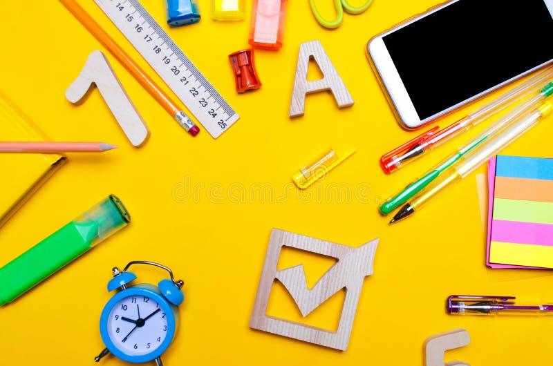 Szkolny wybory pojęcie Wybory czeka szkoły i pudełka akcesoria na biurku na żółtym tle Edukacja materiały, zegarek obraz stock