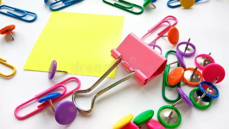 Szkolnych i biurowych dostaw papierowe klamerki, szpilki, żółte notatki, majchery na białym tle zdjęcie royalty free