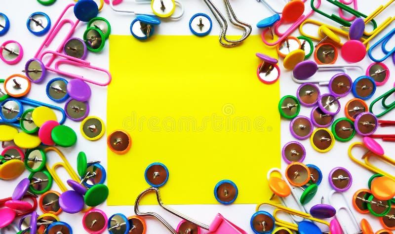 Szkolnych i biurowych dostaw papierowe klamerki, szpilki, żółte notatki, majchery na białym tle obrazy stock