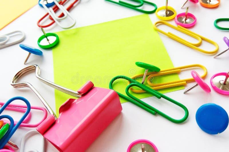 Szkolnych i biurowych dostaw papierowe klamerki, szpilki, notatki, majchery na białym tle fotografia stock
