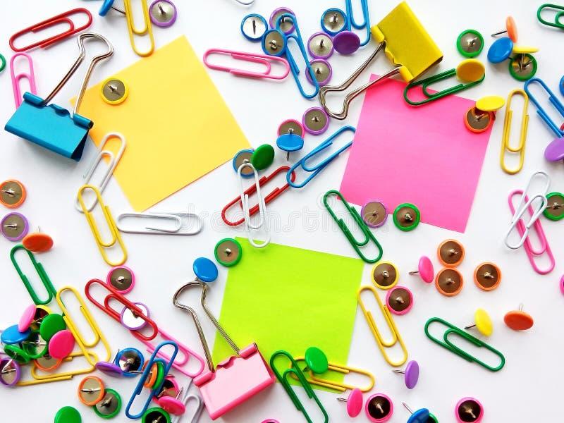 Szkolnych i biurowych dostaw papierowe klamerki, szpilki, notatki, majchery na białym tle zdjęcia royalty free