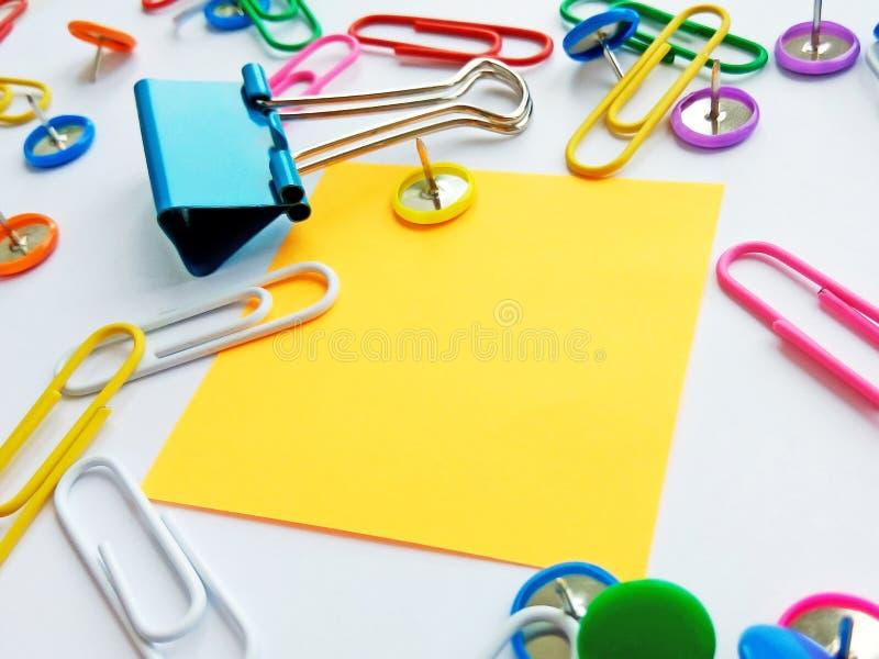 Szkolnych i biurowych dostaw papierowe klamerki, szpilki, notatki, majchery na białym tle zdjęcie royalty free