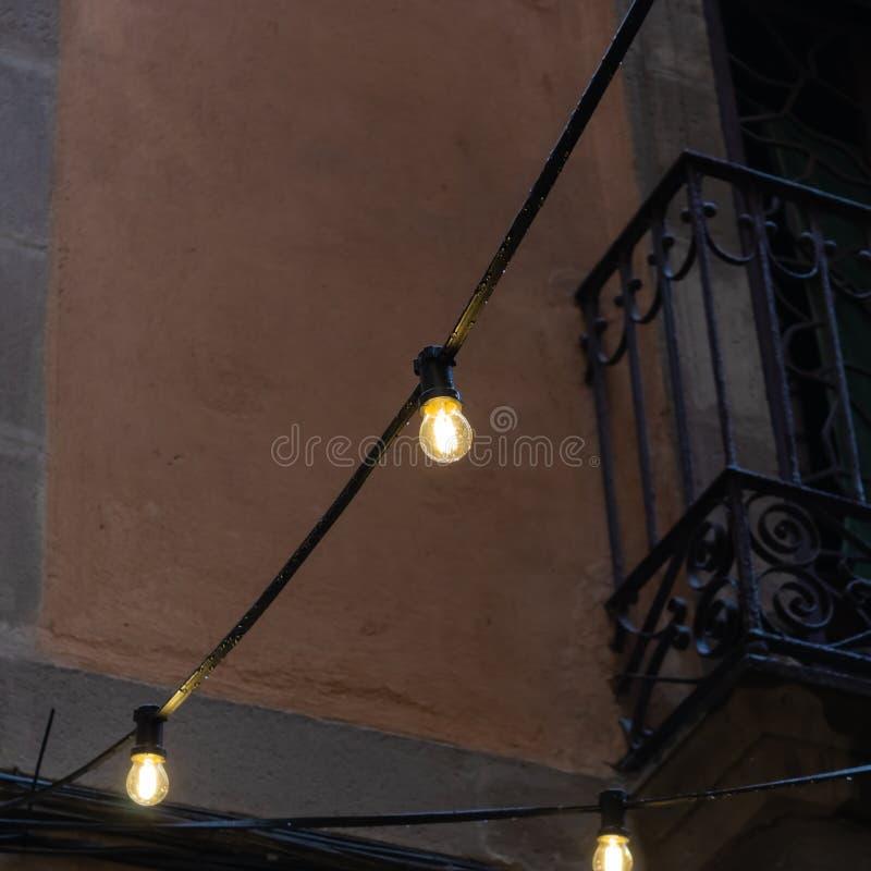 Sznurek trzy żarówki światła z balkonem na tle - wizerunek zdjęcia stock