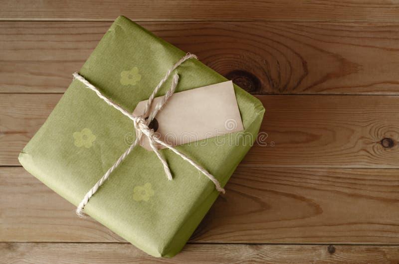 Sznurek Wiążący pakuneczek z etykietką i Zielonym Kwiecistym Opakunkowym papierem zdjęcia stock