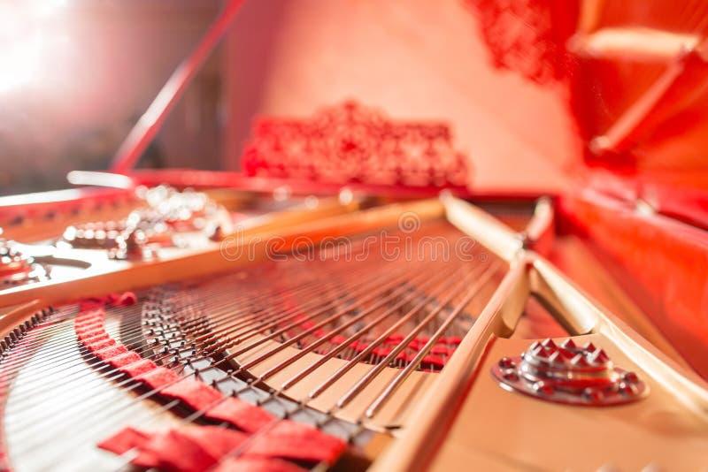 Sznurki wśrodku czerwonego uroczystego pianina Fortepianowy bawić się, zwilżacze, filc młoty, brązów sznurki i metal rama, zdjęcia royalty free