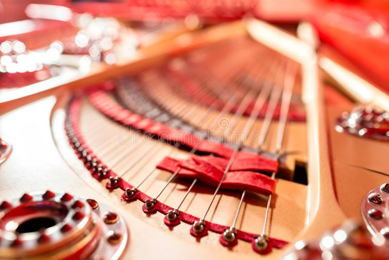 Sznurki wśrodku czerwonego uroczystego pianina Fortepianowy bawić się, zwilżacze, filc młoty, brązów sznurki i metal rama, obrazy royalty free