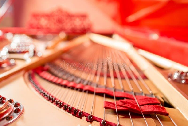 Sznurki wśrodku czerwonego uroczystego pianina Fortepianowy bawić się, zwilżacze, filc młoty, brązów sznurki i metal rama, zdjęcia stock