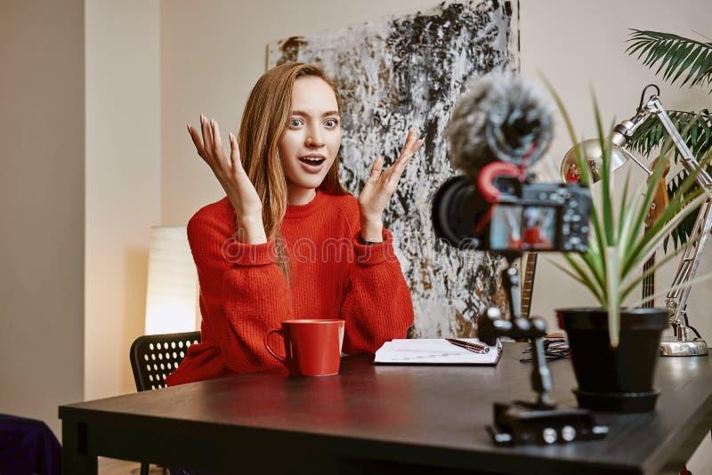 Szok wiadomość! Zdziwiony żeński blogger gestykuluje podczas gdy tworzący nowego mówienie na kamerze i wideo zdjęcie stock