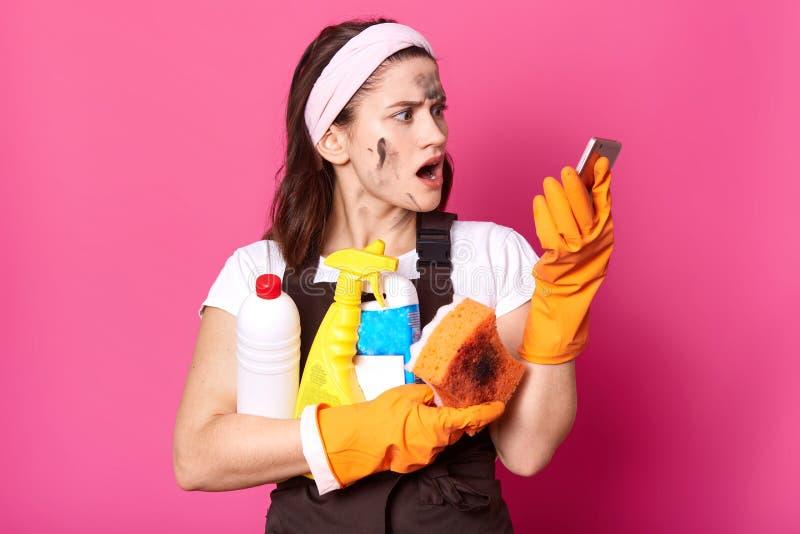 Szokować nikłe brunetki gospodyni domowej chwytów butelki czyści detergent w jeden ręce telefonie w inny jeden i, spojrzenia szok zdjęcie royalty free