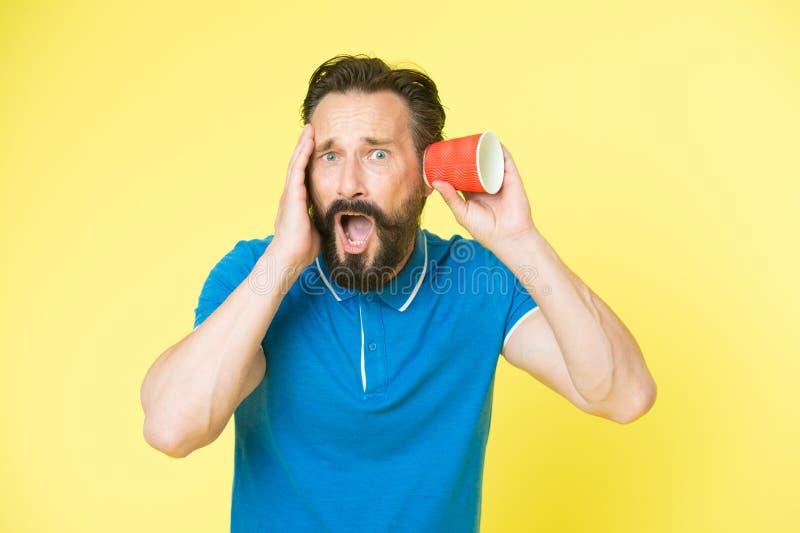 Szokować plotki Mężczyzna brodaty dojrzały facet podsłuchuje z filiżanka koloru żółtego tłem Znajduje out nowych gorsząçy plotek  zdjęcia stock