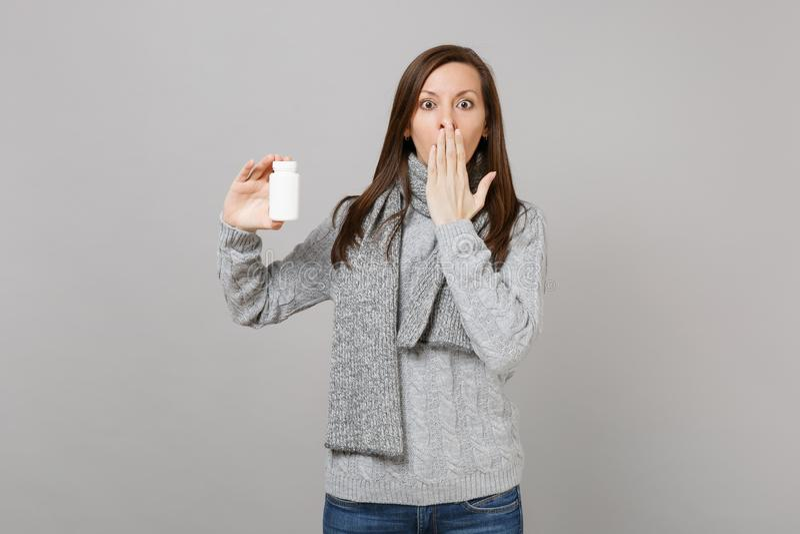 Szokująca kobieta w pulowerze, szalika nakrywkowy usta z ręka chwyta lekarstwa pastylek aspiryny pigułkami w butelce odizolowywaj obraz royalty free
