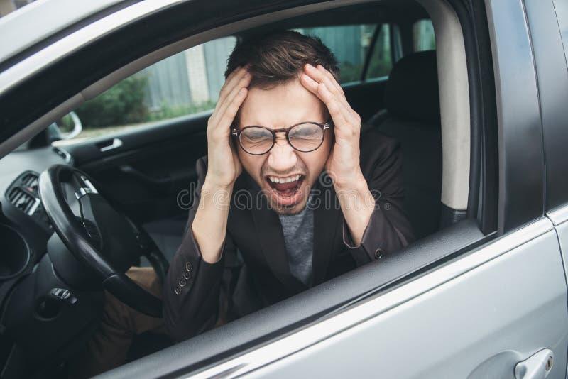 Szokujący młody facet siedzi przy jego samochodem Jego ręki są na jego głowie, jego usta są szeroko otwarty pojęcia migreny odoso zdjęcie stock
