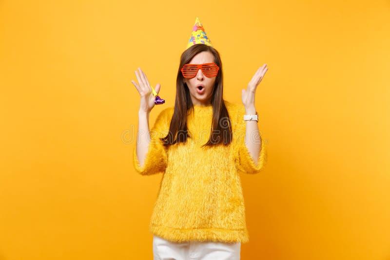Szokuję intrygował kobiety w pomarańczowych śmiesznych szkłach, urodzinowy kapelusz z bawić się fajczane podesłanie ręki, odświęt zdjęcie royalty free