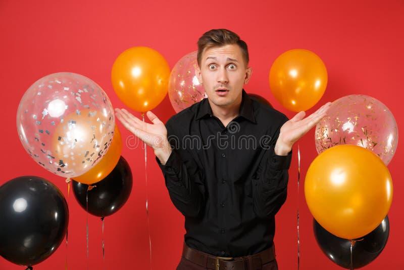 Szokuję oszołamiał młodego człowieka w klasycznych koszulowych podesłanie rękach na jaskrawego czerwonego tła lotniczych balonach obrazy stock