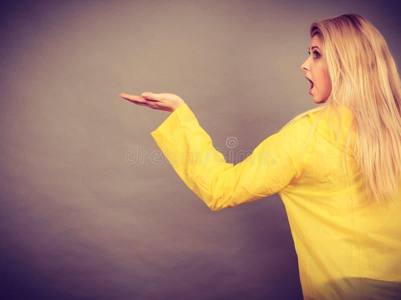 Szokująca kobieta jest ubranym żółtą deszczowa seansu rękę obrazy royalty free