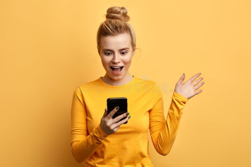 Szokująca młoda emocjonalna dziewczyna patrzeje telefon komórkowego fotografia stock