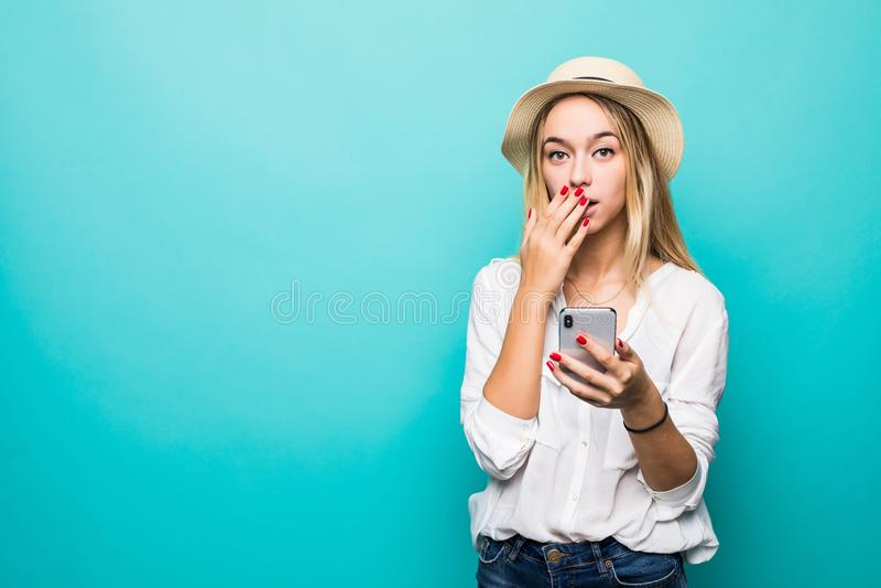 Szokująca młoda kobieta w słomianym kapeluszu używać telefon komórkowego odizolowywającego nad błękitnym tłem obrazy royalty free