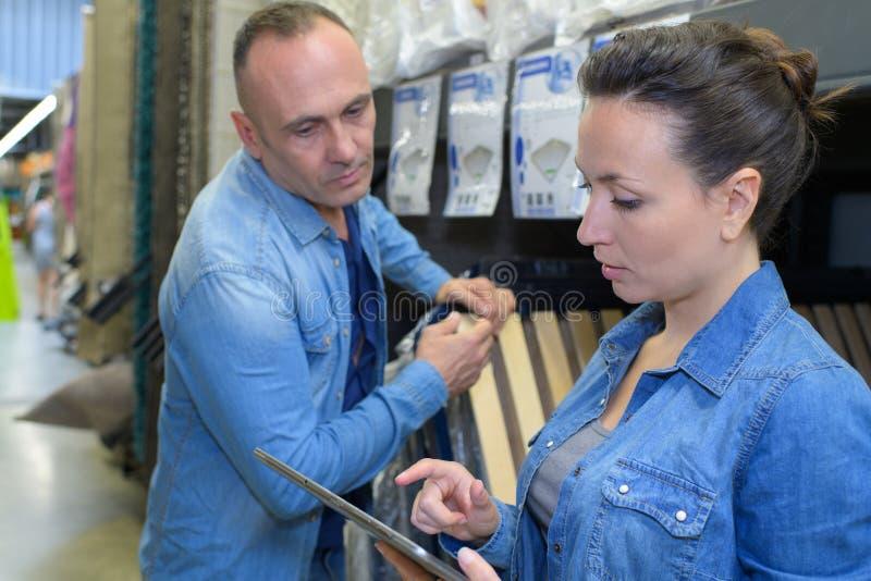 Szokująca w średnim wieku kobiety mienia cena przy meblarskim sklepem zdjęcie stock