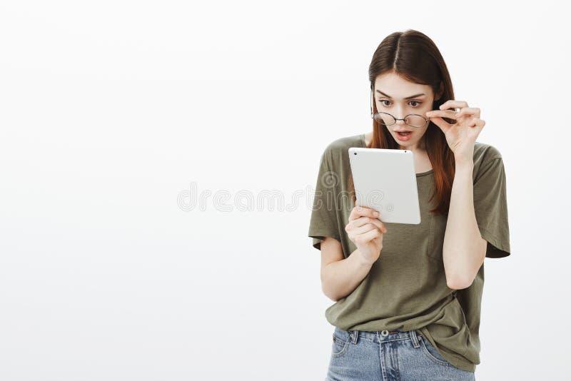 Szokująca wiadomość w sieć imponującej młodej dziewczynie Portret zdziwiona powabna kobieta, bierze daleko szkła i gapić się fotografia stock
