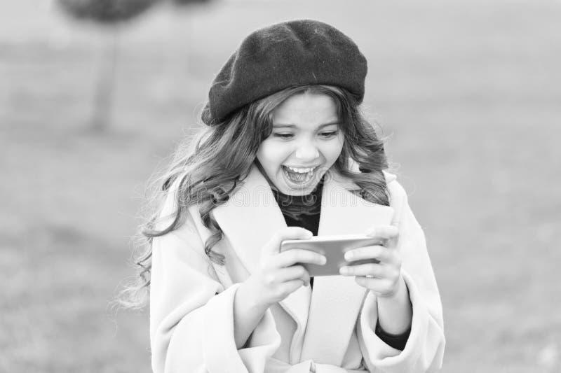 Szokująca zawartość Little girl using mobile phone Mała dziewczynka sprawdza źródła wiadomości Surfing internet Sieci społecznośc fotografia stock