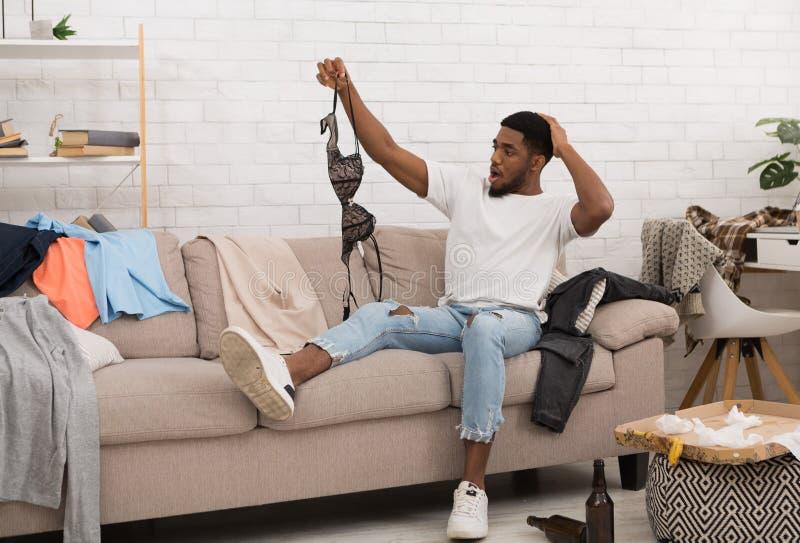 Szokującej mężczyzny mienia kobiety stanik dalej po domowego przyjęcia zdjęcia royalty free