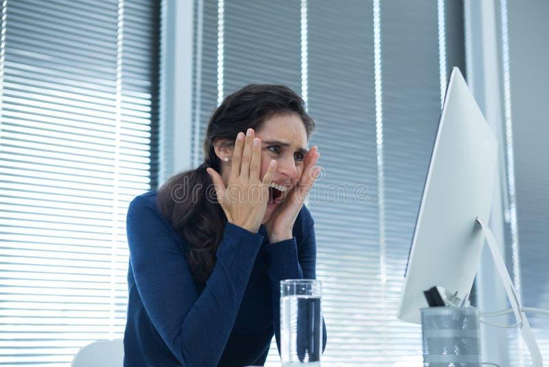 Szokujący żeński wykonawczy patrzeje komputer stacjonarny zdjęcia stock