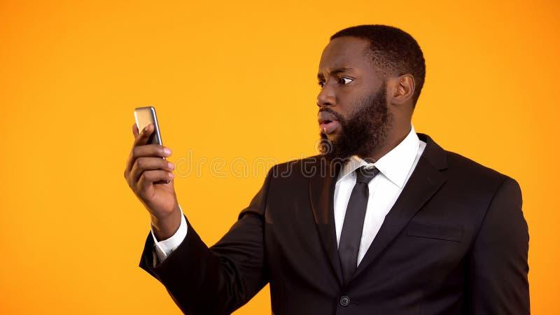Szokujący afroamerykański męski czytelniczy email na telefonie, mobilny app, zdziwienie zdjęcie royalty free