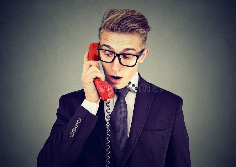 Szokujący biznesowy mężczyzna opowiada na telefonie fotografia stock