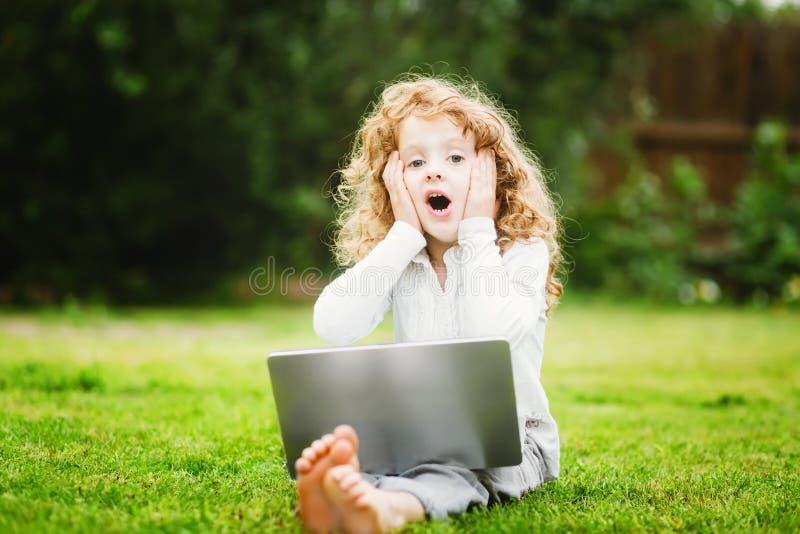 Szokujący i szczęśliwy zdziwiony dziecko z laptopu obsiadaniem na grą fotografia stock